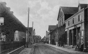Das Foto zeigt die westliche Kirchstraße in Detern im Jahre 1912. Rechts ist das 1899 errichtete Geschäftshaus Onno Siebels (später Temme Groothoff) zu sehen, darauf folgend die nach einem Brand 1902 an gleicher Stelle neu errichtete Apotheke. Auf der linken Seite ist ein kleiner Teil des mit schmiedeeisernem Gitter eingefassten Friedhofes sowie das Schulhaus mit Lehrerwohnung, das 1970 abgebrochen wurde, abgebildet.